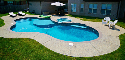 Refreshing oasis in backyard with pool hot tub and patio furniture.